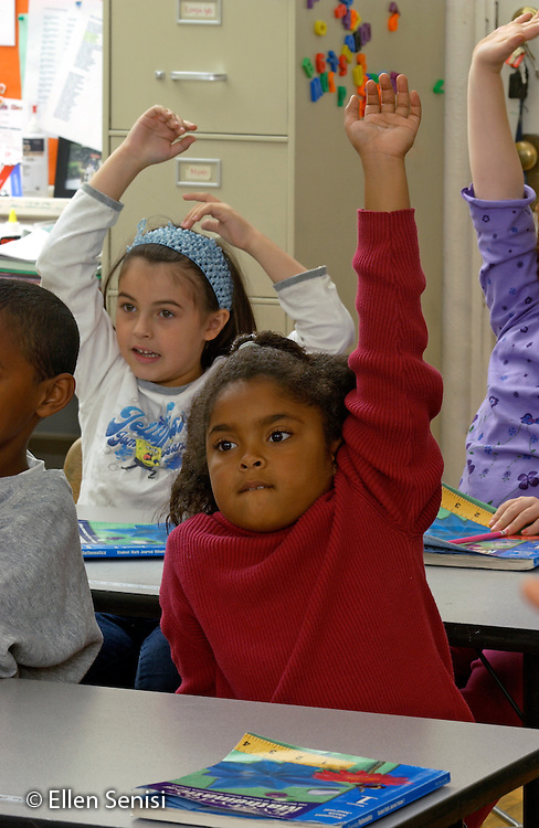 MR / Schenectady, NY.Yates Arts in Education Magnet School, Grade 2.Arts-Themed Urban Elementary School.Students raise hands to answer questions during math lesson..Girl foreground: 7, African-American, Puerto Rican American, and Caucasian..MR: Gri9.© Ellen B. Senisi