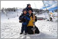 A young child/toddler has his first lesson in snow skiing. Photo taken in Pennsylvania, but can be used to illustrate children learning how to ski anywhere. Model released image. Here, the father poses with his children before hitting the slopes.