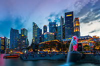 Merlion statue fountain lit up in pink at sunset, with business district skyline in the background in Merlion Park, Singapore Southeast Asia