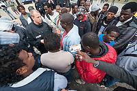 """Am Montag den 25. August 2014 wurde den Fluechtlingen vom ehemaligen Protestcamp auf dem Kreuzberger Oranienplatz beschieden, dass ihre Antraege auf Asyl von der Stadt Berlin nicht anerkannt werden. Die Auslaenderbehoerde teilte mit, dass das Land Berlin somit keinerlei soziale Leistungen, z.B. Unterkunft, Geld oder Krankenversicherung, mehr erbringen werde.<br /> Aus Protest zogen die Betroffenen daraufhin zum Oranienplatz und protestierten gegen diese Entscheidung. Sie errichteten mit einer Plastikplane ein symbolisches Zelt und erklaerten, dass sie nicht mehr gehen wollten. Als die Polizei die Plane konfiszierte eskalierte die bis dahin friedliche Situation und etliche Fluechtlinge und unbeteiligte Zuschauer wurden unter Einsatz von Tritten, Schlaegen und Pfefferspray festgenommen. Auch wurden Journalisten mit Worten wie """"Hau ab du Arsch!"""" beschimpft.<br /> Im Bild: Fluechtlinge zeigen Polizisten ihre Hausausweise aus der Unterkunft, die sie nach ihren Worten nun nicht mehr nutzen duerfen.<br /> 25.8.2014, Berlin<br /> Copyright: Christian-Ditsch.de<br /> [Inhaltsveraendernde Manipulation des Fotos nur nach ausdruecklicher Genehmigung des Fotografen. Vereinbarungen ueber Abtretung von Persoenlichkeitsrechten/Model Release der abgebildeten Person/Personen liegen nicht vor. NO MODEL RELEASE! Don't publish without copyright Christian-Ditsch.de, Veroeffentlichung nur mit Fotografennennung, sowie gegen Honorar, MwSt. und Beleg. Konto: I N G - D i B a, IBAN DE58500105175400192269, BIC INGDDEFFXXX, Kontakt: post@christian-ditsch.de<br /> Urhebervermerk wird gemaess Paragraph 13 UHG verlangt.]"""