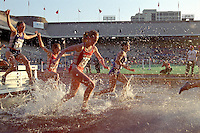 Runners splash through the pit in the College Women's Steeplechase Championship of America at the 2001 Penn Relays in Philadelphia.