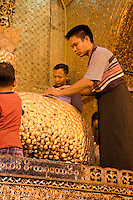 Myanmar, Burma.  Mandalay.  Mahamuni Buddhist Temple.  Men apply gold leaf to Buddha statue.  Only males are allowed to approach the Mahamuni Buddha.