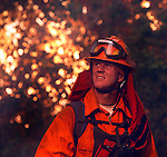 A firefighter fights a forest fire in California.