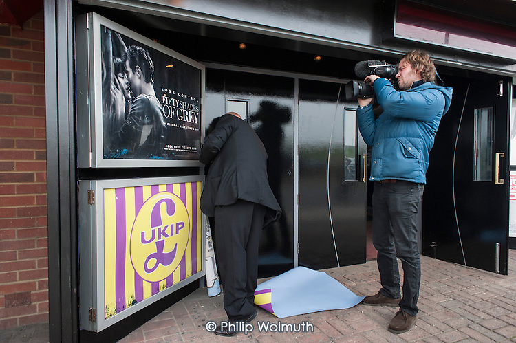 A member of staff removes UKIP posters outside the Movie Starr cinema, Canvey Island, South Essex, following the launch of the party's General Election campaign a the seafront venue.