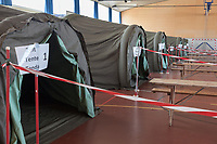 """Switzerland. Canton Ticino. Rivera. Monte Ceneri military base. Due to the spread of the coronavirus (also called Covid-19), the Federal Council has categorised the situation in the country as """"extraordinary"""". The army was called upon to provide logistical support and to offer its skills in terms of medical assistance (ambulances, field hospital, tents, nurses,..). The militia soldiers from medical troops were called by the Swiss army for the first time since World War II. Under the country's militia system, professional soldiers constitute a small part of the military and the rest are conscripts or volunteers aged 19 to 34 (in some cases up to 50). Seven tents have been set up for soldiers in the gym hall. The tents will only be used as isolation tents in cases of coronavirus contamination. Monte Ceneri is a mountain pass in the canton of Ticino. It connects the Magadino plain and the Vedeggio valley across the Prealps. 2.04.2020 © 2020 Didier Ruef"""