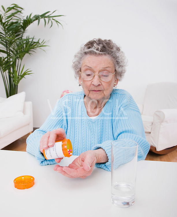 Senior woman pouring pills into hand