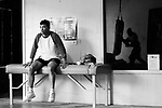 ARTURO GATTI (5/12) --WBC super lightweight boxing champion Arturo Gatti (left) watches as James McGirt (reflected in window) hits the heavy bag at McGirt's father's boxing gym in Vero Beach, FL.  (4/12/05)  VERO BEACH, FL