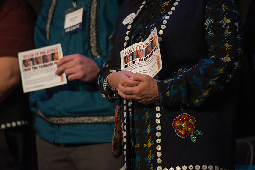 """AFN delegates take the stage alongside Lt. Governor Byron Mallott and Governor Bill Walker holding fliers in support of the """"Fairbanks Four"""" during a surprise protest at the 2015 Alaska Federation of Natives Convention."""