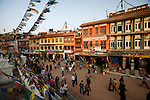 People walk around Boudhanath Stupa (or Bodnath Stupa) the largest stupa in Nepal, as the sun sets in Kathmandu.