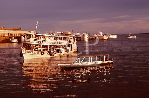 Manaus, Brazil. Cortez Filho 'Gaiola' riverboat and a smaller boat at dusk. Amazonas State.