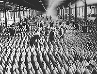 English women in munition factory.  Women and men working in storage shed for large shells.  In most of the munition centers the Y.W.C.A. has established cafeterias and shampoo parlors.  Ca.  1918-19.  (Women's Bureau)<br /> Exact Date Shot Unknown
