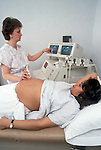 Young pregnant woman looks at screen during ultrasound procedure