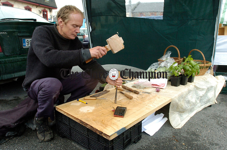 Bernard Booth gets in a spot of woodcarving while looking after his stall at the Ennis Farmers Market. Photograph by John Kelly.