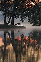A light mist rises off a lake at dawn.