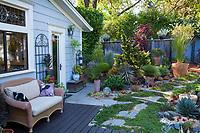 Wicker bench opn patio deck overlooking California plant collector backyard garden - Carol Brant
