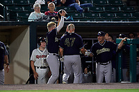 Scranton/Wilkes-Barre RailRiders Trey Amburgey (29) takes the helmet off Erik Kratz (47) as he is congratulated by coach Doug Davis (right) after hitting a home run during an International League game against the Rochester Red Wings on June 24, 2019 at Frontier Field in Rochester, New York.  Rochester defeated Scranton 8-6.  (Mike Janes/Four Seam Images)