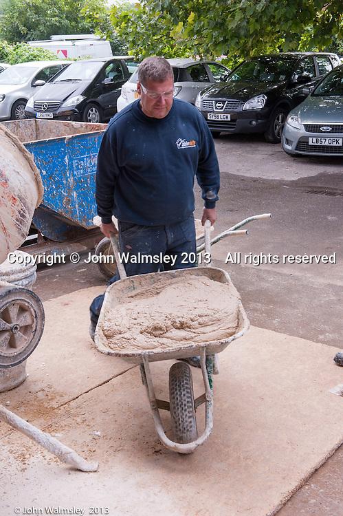 Plastering instructor moving the freshly mixed plaster inside.  Able Skills training centre, Dartford, Kent.