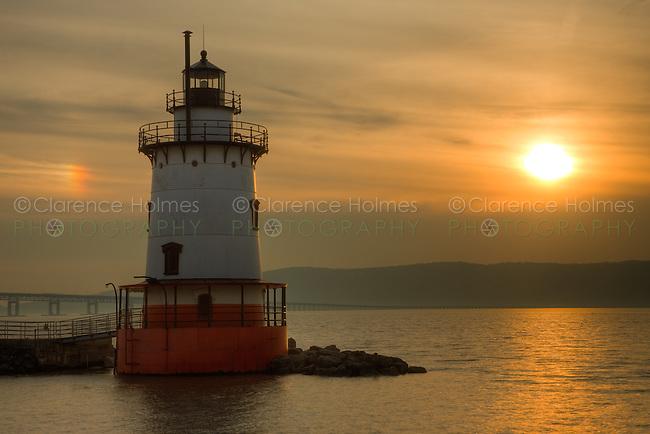 Tarrytown Lighthouse on the Hudson River under a hazy sky and parhelion near sunset.