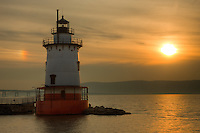 Tarrytown Lighthouse on the Hudson River under a hazy sky and parhelion near sunset.