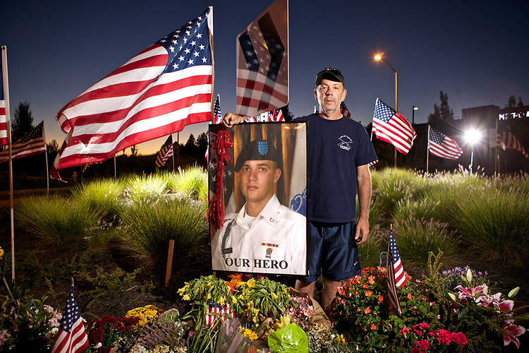 08/21/12--Jeff Keller stands by a photo of his son, Andrew, at memorial for him that is located on a roundabout on Southwest Barrows Road near The Village on Scholls Ferry in Beaverton. Andrew was killed in action Aug. 15 while serving with the Army in Afghanistan. Keller graduated from Southridge High School in 2008....Photo by Jaime Valdez... ..