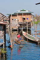 Myanmar, Burma.  Village Scene, House on Stilts, Transport by Boat, Inle Lake, Shan State.  The young man is rowing in the one-legged style common to the Inle Lake area.