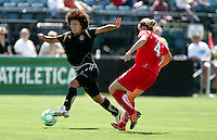Eriko Arakawa (left) tries to dribble past Cat Whitehill (4). FC Gold Pride defeated Washington Freedom 3-2 at Buck Shaw Stadium in Santa Clara, California on August 1, 2009.