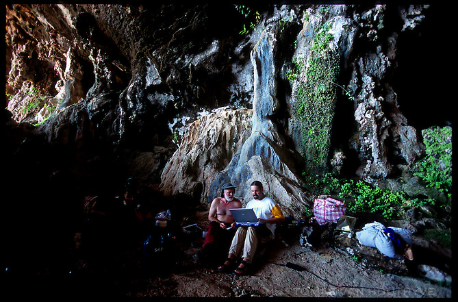 Speolologists Peter De Geest, right, and Chris Butanaru line up GPS (Global Positioning System) coordinates with a three dimensional digital map in a laptop computer at the mouth of Hoq cave in Socotra, Yemen on Monday, 16 May 2005.<br />
