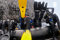 Group of scuba divers diving backwards off dinghy, low section (Licence this image exclusively with Getty: http://www.gettyimages.com/detail/200503609-001 )