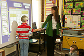 MR / Schenectady, NY. Zoller Elementary School (urban public school). Kindergarten inclusion classroom. Teacher gives student (boy, 5) interactive whiteboard pen tool so he can mark the date on the calendar at digital white board. This is part of a daily routine to help reinforce a basic concepts about time by frequent repetition. MR: Ger2, War15. ID: AM-gKw. © Ellen B. Senisi.