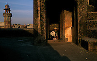 A man steps into the doorway of a rooftop of a mosque to pray at sunset.