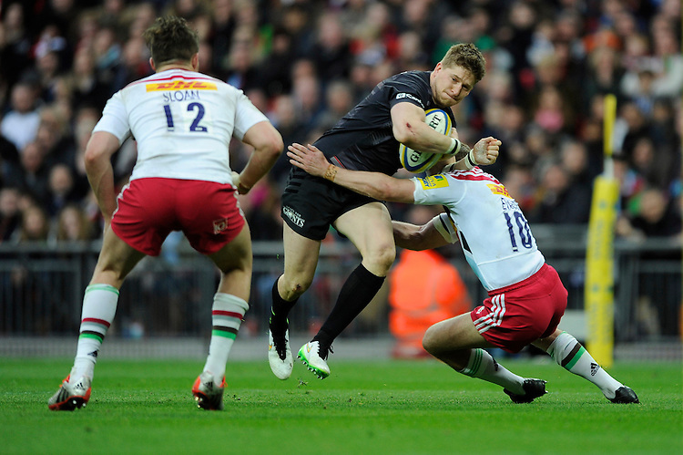 David Strettle of Saracens is tackled by Nick Evans of Harlequins as Harry Sloan of Harlequins supports