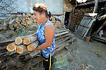 """Mitka Ivanova lives in the Bulgarian town of Staro Oriahovo, where residents consider the term """"Roma""""  to be negative and thus refer to themselves as Romanian-speaking Bulgarians. here she collects wood to take inside her home."""