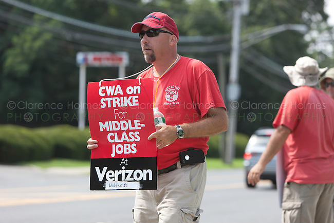 HARTSDALE, NY - AUGUST 9: An on-strike Verizon employee, a member of the Communications Workers of America (CWA), pickets on the street in front of a Verizon Wireless store in Hartsdale, New York.  The strike began on August 7th, 2011 due to the CWA's unhappiness with Verizon management's stance in bargaining a new contract.