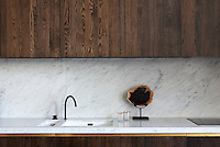 The bespoke joinery in the kitchen is subtle and unfussy and the oak wood is set off by the grey marble work surface and splashback.