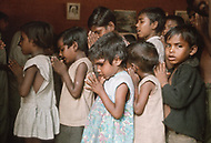 """Calcutta, India. April 04, 1975.<br /> Orphaned children praying and singing Catholic songs under the framed image of Mother Teresa, the founder of the orphanage. Mother Teresa (Agnes Gonxha Boyaxihu) the Roman Catholic, Albanian nun revered as India's """"Saint of the Slums,"""" was awarded the 1979 Nobel Peace Prize."""