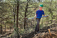 Photo story of Philmont Scout Ranch in Cimarron, New Mexico, taken during a Boy Scout Troop backpack trip in the summer of 2013. Photo is part of a comprehensive picture package which shows in-depth photography of a BSA Ventures crew on a trek.  In this photo a BSA Venture Crew member works to clear dirt from a new trail being cut during the Venture Crews conservation project in the backcountry at Philmont Scout Ranch.   <br /> <br /> The  Photo by travel photograph: PatrickschneiderPhoto.com