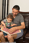 18 month old toddler boy looking at book with father pointing at illustration