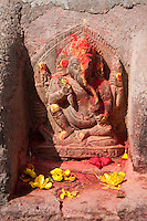 Kathmandu, Nepal.  Stone Sculpture of the God Ganesh, with Flowers and Sindur Offerings.