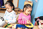 Education preschool 3-4 year olds two girls playing separately at sink in pretend play area cooking with leaves and stones