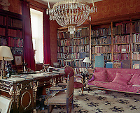 The library is filled with faded Empire furniture and the walls are covered in a pink and yellow damask
