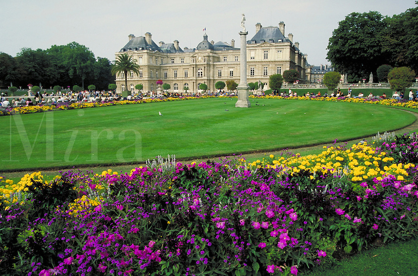 Luxembourg Palace and Gardens. Colorful flowerbed rings large grass area with column topped by classical statue. Palms and other trees. Seagull and pigeons on grass and column. People in distance look at pool around fountain. Paris, France.