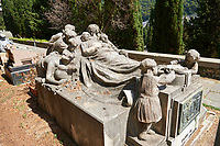 Pictures of the stone sculpture of a dead man lying whilst surrounded by his grieving family. The Lavarello tomb sculpted by Brizzolara 1926. The monumental tombs of the Staglieno Monumental Cemetery, Genoa, Italy