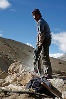 "Workers break rocks to build the road to Everest Base Camp.<br /> China started building a controversial 67-mile ""paved highway fenced with undulating guardrails"" to Mount Qomolangma, known in the west as Mount Everest, to help facilitate next year's Olympic Games torch relay.<br /> Tibet, China<br /> July, 2007"