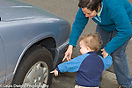 22 month old toddler boy outside with mother interested in car pointing and naming wheel