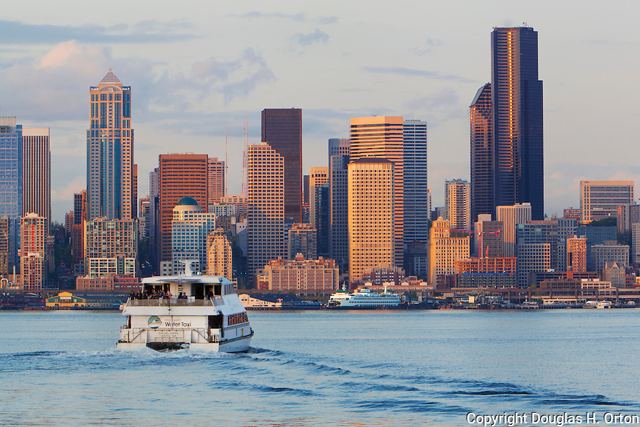 Seattle Skyline, Elliott Bay with King County Water Taxi and Washington State Ferry, Alaskan Way Viaduct and downtown buildings at dusk.