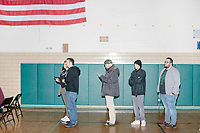 People register to vote in the New Hampshire Presidential Primary at Fair Grounds Junior High School in Nashua, New Hampshire, on Tue., Feb. 11, 2020.