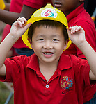 A student display a hardhat during a groundbreaking ceremony for the new Mandarin Chinese Language Immersion Magnet School, December 6, 2014.