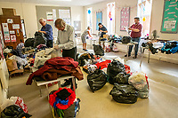 BNPS.co.uk (01202 558833)<br /> Pic: MaxWillcock/BNPS<br /> <br /> Pictured: Volunteers sorting donations.<br /> <br /> A flood of donations for Afghan refugees has inundated a church which has been left with a 24ft long stack of parcels.<br /> <br /> Ross Donaldson posted on a Facebook community group asking if anyone had clothes to offer, sparking an overwhelming response from his community.<br /> <br /> After organising to keep donations at Immanuel Church, Bournemouth, Dorset, he arrived the next morning to find a pile of bags.