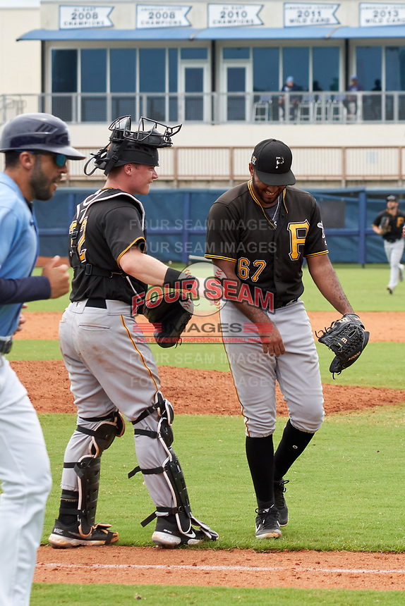 FCL Pirates Black catcher Henry Davis (32) jokes with pitcher Kelvin Disla (67) as they walk to the dugout after the bottom of the fifth inning during a game against the FCL Rays on August 3, 2021 at Charlotte Sports Park in Port Charlotte, Florida.  Davis was making his professional debut after being selected first overall in the MLB Draft out of Louisville by the Pittsburgh Pirates.  (Mike Janes/Four Seam Images)