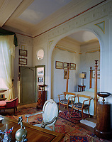 Enclosed in a trompe l'oeil hanging of eau-de-nil silk, the early 19th-century four poster bed, featuring decorative urns atop the posts, was made in Lucca as were the Empire armchairs at its base. The carpet is Anatolian.
